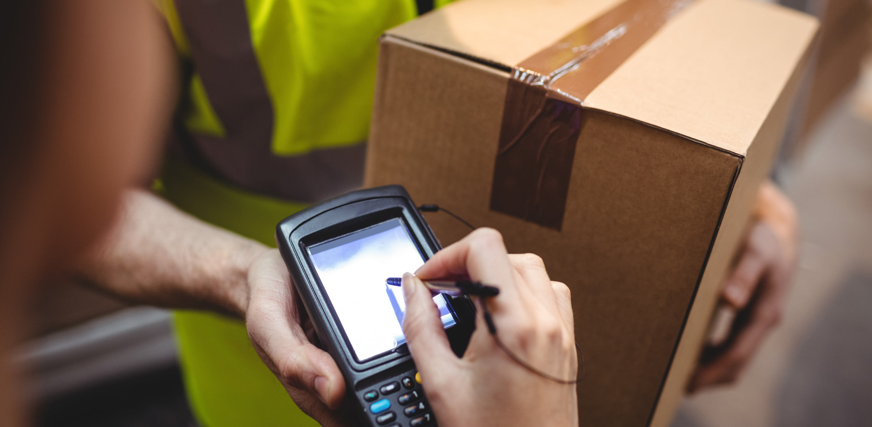 An image showing a Parcel being delivered and being signed for on a delivery tracking device.