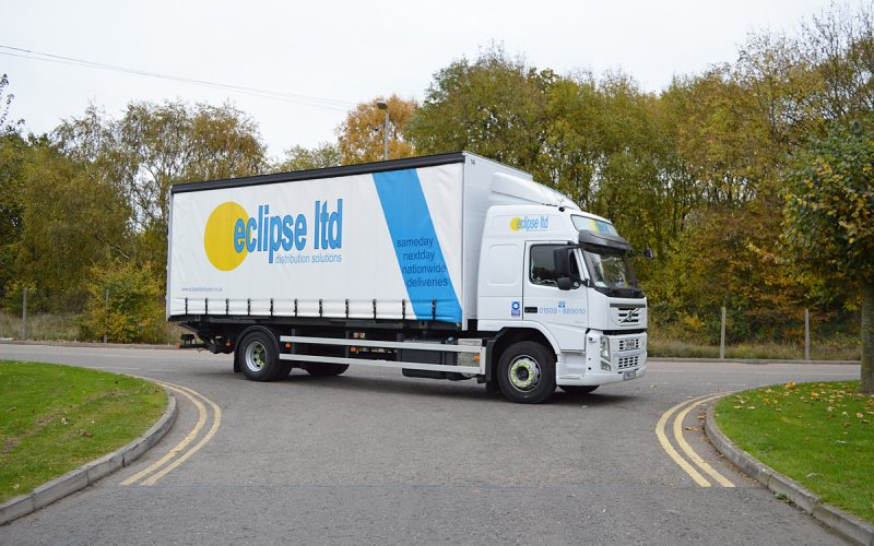 An image showing a lorry delivery with a curtain side on the road