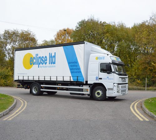 An image showing a lorry delivery with a curtain side on the road.